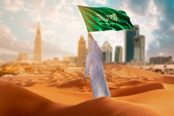 Saudi young Arab man holding Saudi Arabia  flag, celebrating the national day