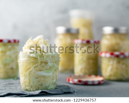 Sauerkraut in open glass mason jar. Pickling cabbage at home on table. The best natural probiotic. Homemade kraut., copy space for text