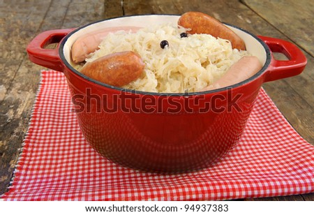 sauerkraut in red stew pot on old table