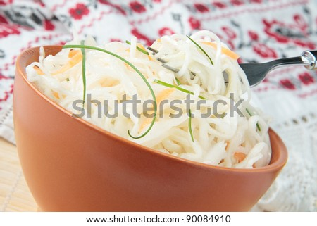 Sauerkraut with carrots in a ceramic bowl