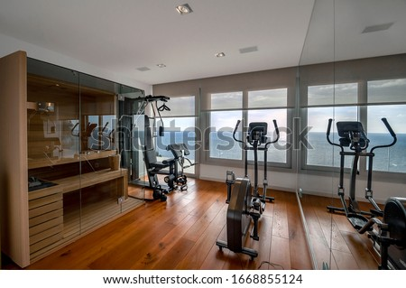 Sauna and fitness room with sea view. Traditional finnish sauna made from woodand glass door design in the sauna.  Concept of: relax, vacation, wellness center.  Foto d'archivio ©