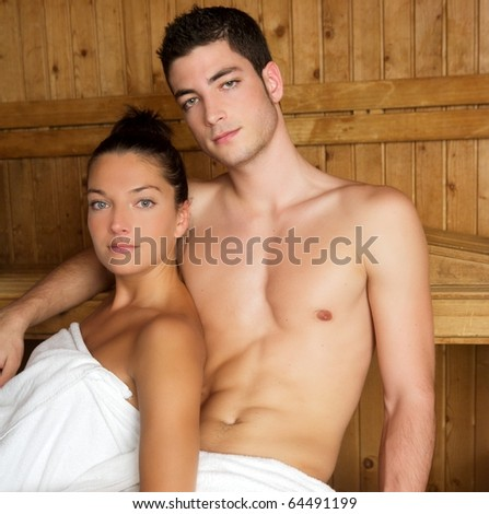 Sauna spa therapy young couple in warm wooden room white towel
