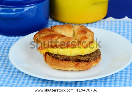 Sausage Egg and Cheese on golden brown Croissant with colorful place mat and ceramic bowls.