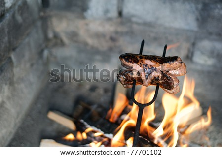 Sausage roasted over a fire in the fireplace