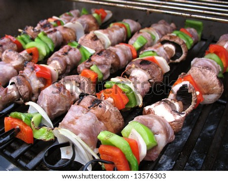 Sausage shish kebabs on skewers, cooking on the grill.  Shallow depth of field.