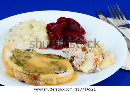 Sausage, spinach, onion and garlic stuffing rolled into boneless turkey breast and served with potatoes; cranberry sauce; and fruit salad.  White plate against blue background.