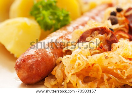 Sausage with potatoes and sauerkraut and bread loaves