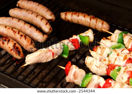Sausages and chicken kebabs on a barbecue