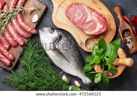 Sausages, fish, meat and ingredients cooking. Top view on stone table #472568125
