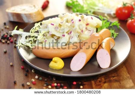 Sausages, frankfurter and salad on plate, closeup.