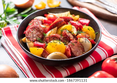 Sausages fried with peppers, tomatoes, and onions in a black plate on a dark background close-up. Sausages stewed with vegetables. Traditional Hungarian food lecho. Foto d'archivio ©