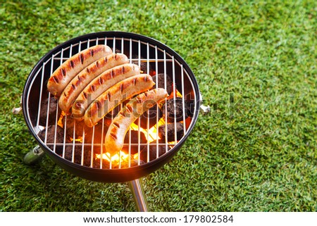 Sausages grilling over the hot glowing coals in a portable barbecue standing on a green lawn with copyspace during a picnic or summer camping trip