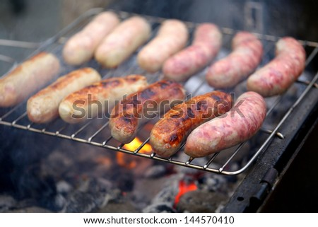 Sausages on grill on a whole background