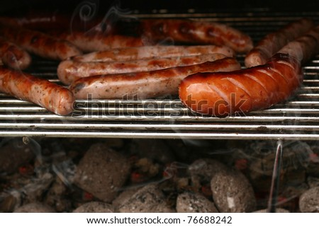 Sausages on grill, with smoke