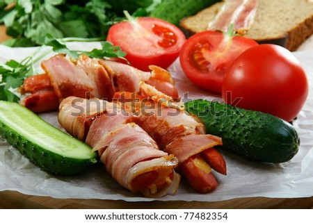 Sausages wrapped in bacon with vegetables and herbs on a wooden table.