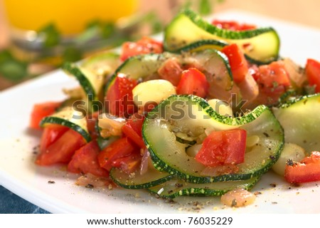 Sauteed zucchini slices, tomato cubes, onion and cooked corn grains with dried herbs and black pepper (Selective Focus, Focus on the front of the zucchini slice and tomato piece in the front)