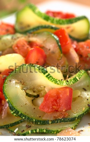Sauteed zucchini slices, tomato cubes, onion and cooked corn grains with dried herbs and black pepper (Selective Focus, Focus on the upper part of the zucchini slice and the tomato cube below)