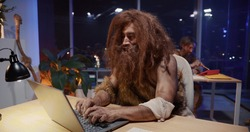 Savage bearded furry neanderthal cave human playing with laptop interacting modern technology working in office interior. Humor concept.