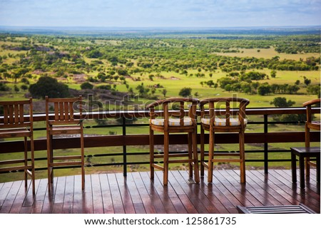 Savanna landscape in Serengeti, Tanzania, Africa. Chairs on the terrace for observation