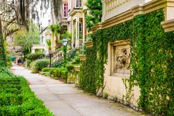 Savannah, Georgia, USA historic downtown sidewalks and rowhouses.