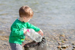 Save environment concept, a little boy collecting garbage and plastic bottles on the beach to dumped into the trash