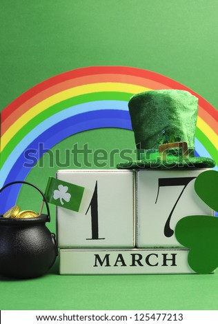 Save the date white block calendar for St Patrick's Day, March 17, with Leprechaun hat, pot of gold, and rainbow, on green background. Vertical portrait orientation.