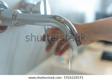 Save the water concept.Hand closing valve on sink in bathroom. Water dripping to stop running as hand turn off the faucet. Detect a Leak week. Stock photo ©