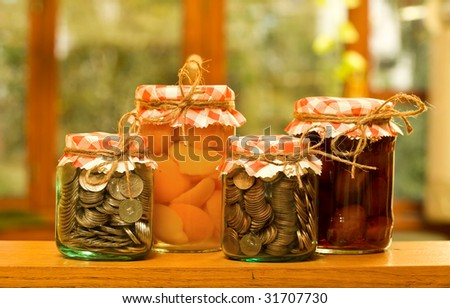 Save when you have plenty - money saving concept with canned fruits and money in glass jars