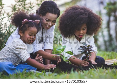 Save world concept - Mother and daughter are planting fun little trees on the fence of his house. Cute children planted a small tree on the black soil while watering the plants intently. #1570103557