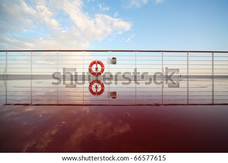saving buoy in deck of cruise ship. deck shining by morning sun. reflection in deck