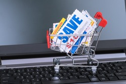 Saving discount coupon voucher in shopping cart and computer notebook, coupons are mock-up
