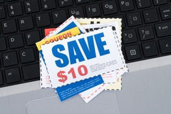 Saving discount coupon voucher on notebook keyboard, coupons are mock-up