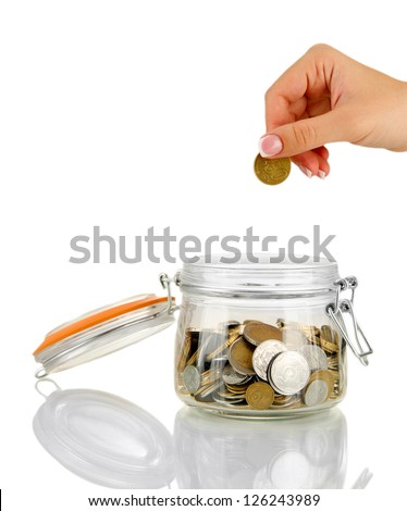 Saving, female hand putting a coin into glass bottle, isolated on white