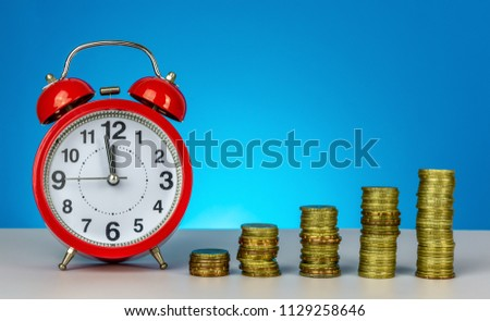 Saving for future. Saving time to saving concept. Clock and stacking coin on blue background. #1129258646