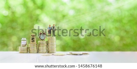Saving for retirement and pension fund concept : Senior retired couple, vintage clock, US dollar money bag, deposit saving jar on steps of rising coins, depicts long-term investment for aging society