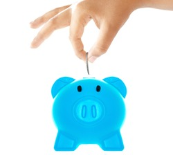 Saving money by putting coin into piggy bank.