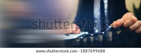 Saving money concept. Hand putting money coin stack with  growing business graph. Panoramic business banner with  copy space.