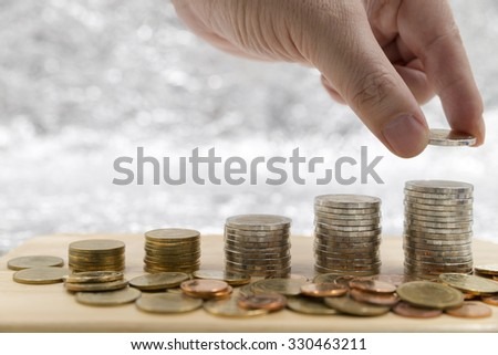 Saving money concept,male hand putting growth money coin stack