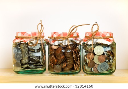 Saving money concept with coins put away in glass jars on a shelf