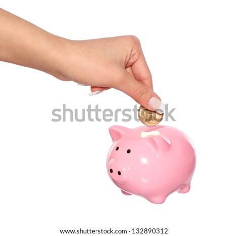 saving money, female  hand is putting coin into piggy bank isolated on white