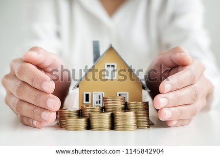 Saving money for house and real estate. Woman hand protecting on  stack coins and house model on table. #1145842904