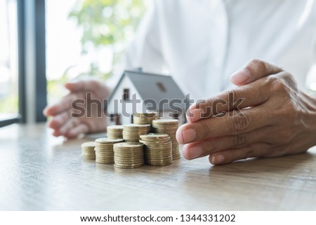 Saving money for house and real estate. Woman hand protecting on stack coins and house model on table. #1344331202