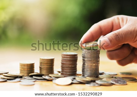 saving money hand putting coins on stack on table with sunshine. concept finance and accounting