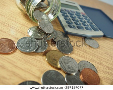 Saving money, pile of coins, Thai money in glassware, calculator on wood background
