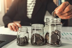 saving money with hand putting coins in jug glass concept financial