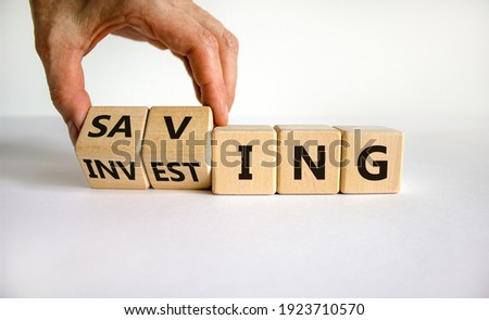 Saving or investing symbol. Businessman turns cubes and changes the word 'investing' to 'saving'. Beautiful white table, white background, copy space. Business and saving or investing concept. Imagine de stoc ©