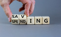 Saving or spending symbol. Businessman turns cubes and changes the word 'spending' to 'saving'. Beautiful grey table, grey background, copy space. Business and saving or spending concept.