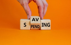 Saving or spending symbol. Businessman turns cubes and changes the word 'spending' to 'saving'. Beautiful orange table, orange background, copy space. Business and saving or spending concept.