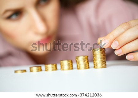 Saving, woman stacking gold coins into increasing columns
