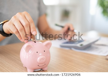 savings and finance concept. woman putting money coin in piggy bank for saving money and plan finance.